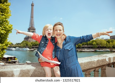 smiling stylish mother and child tourists with map rejoicing against clear view of the Eiffel Tower and river Seine in Paris, France.