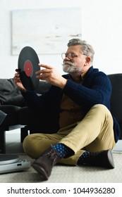 smiling stylish senior man in eyeglasses holding vinyl record while sitting on carpet