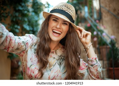 smiling stylish tourist woman in long dress and straw hat in old Europe town taking selfie