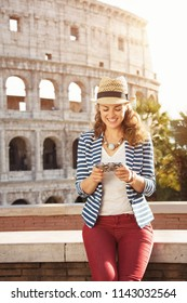 smiling stylish tourist woman in a striped jacket in Rome, Italy writing sms