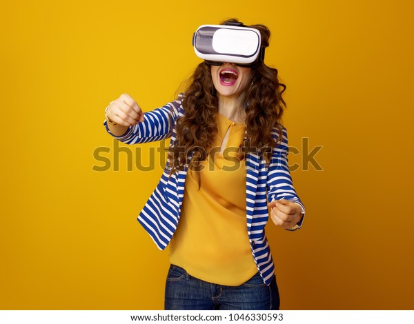 smiling stylish woman with long wavy brunette hair isolated on yellow wearing cardboard VR glasses and driving