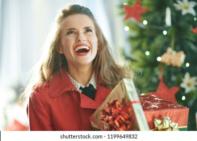 smiling stylish woman in red trench coat with Christmas present boxes looking up near Christmas tree
