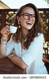 smiling stylish woman in white shirt with eyeglasses sitting at the table drinking coffee in the terrace of guest house hotel.