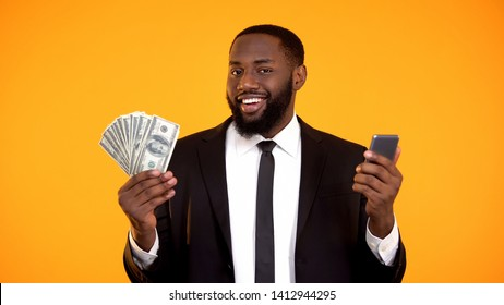 Smiling Successful black male in suit holding phone and dollar bills, cashback