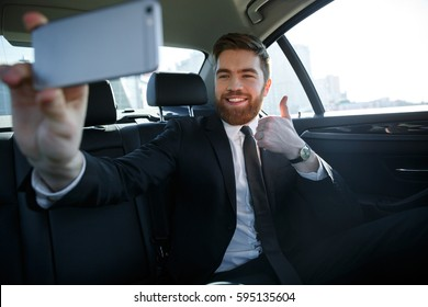 Smiling successful business man taking selfie and showing thumbs up while sitting in the back seat of a car