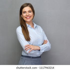 Smiling successful business woman in office dress. Isolated studio portrait with gray wall back.