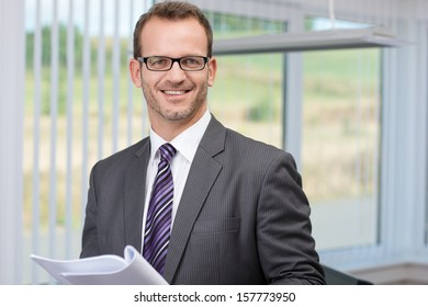 Smiling successful businessman wearing glasses holding a document in his hand looking at the camera with a confident smile