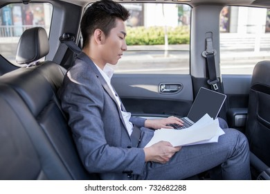 Smiling successful businessman workingthe back seat of car
