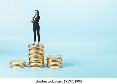 Smiling successful businesswoman in a black suit standing on a pile of coins at abstract blue background. Earning money concept.