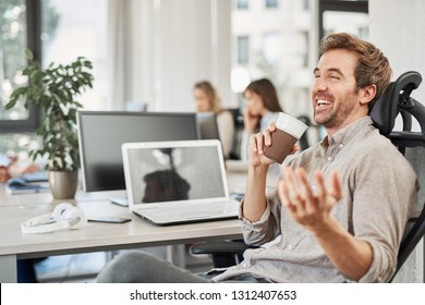 Smiling successful CEO talking to employee and drinking coffee to go while sitting in chair in office. In background workers ar their working stations.