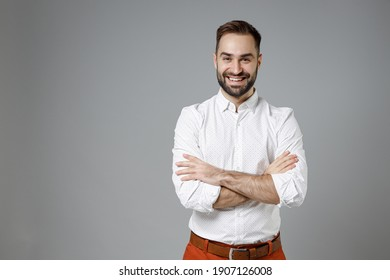Smiling successful confident young bearded business man 20s wearing classic white shirt holding hands crossed isolated on grey color background studio portrait. Achievement career wealth concept