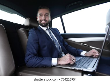 Smiling successful man working with laptop sitting in car