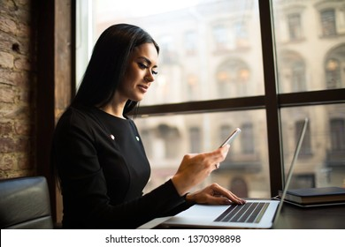Smiling successful woman marketer received notifications on mobile phone during work on laptop computer, sitting in office space. Female government worker checking e-mail on cellphone during webinar