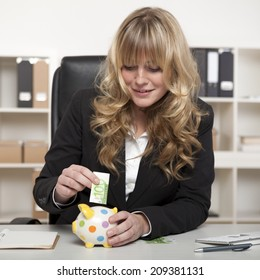 Smiling successful young entrepreneur or businesswoman putting money in a piggy bank, carefully inserting a 100 euro note through the slot.