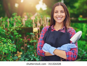 Smiling successful young nursery owner standing amongst her plants with folded arms and a trowel in her hands beaming at the camera