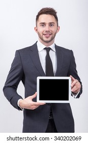 Smiling successful young student on a white background in a classic gray suit and tie presents a tablet screen with a snow-white smile.