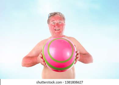 Smiling sunburned man holding a beach ball