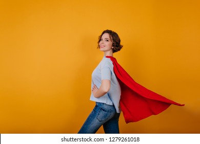 Smiling supergirl in jeans standing in confident pose on yellow background. Indoor photo of curly lady preparing for new year carnival.