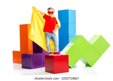 Smiling supergirl wearing yellow cape and red mask for eyes standing on cube isolated on white