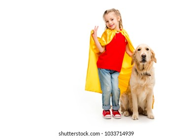 Smiling supergirl in yellow cape gesturing peace sign with golden retriever beside isolated on white
