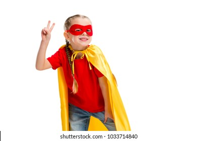 Smiling supergirl in yellow cape and red mask for eyes gesturing peace sign isolated on white