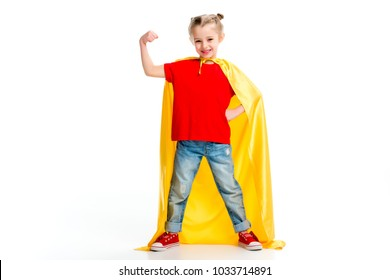 Smiling supergirl in yellow cape showing muscles on hand isolated on white