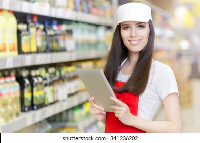 Smiling Supermarket Employee Holding a Pc Tablet - Portrait of a young sales clerk in a market store