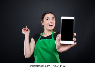 Smiling supermarket female employee showing smartphone with blank screen