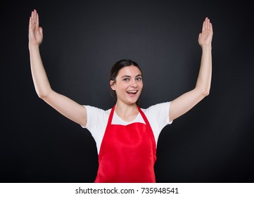 Smiling supermarket seller indicate something big while holding her palms up