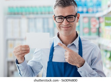 Smiling supermarket worker holding a blank white sign and looking at camera, shelves on the background