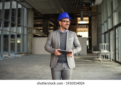 Smiling supervisor walking in building in construction process with tablet in hands and checking on works.