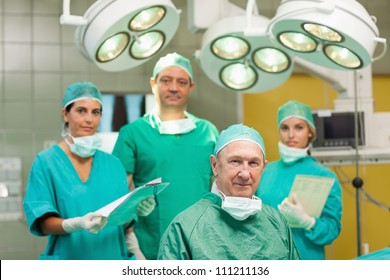 Smiling surgeon sitting with a team behind him in a surgical room