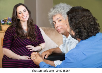 Smiling surrogate mother with gay Hispanic couple