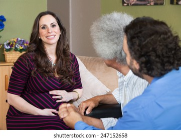 Smiling surrogate mother sitting with homosexual parents