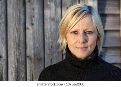 Smiling, Swedish, healthy looking woman in front of a wooden wall on a sunny day, wearing a black sweater.