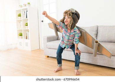 smiling sweet female children wearing astronaut costume making ready to fly gesture standing on living room wooden floor at home.
