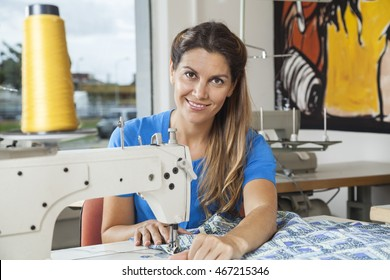 Smiling Tailor Stitching Fabric At Workbench