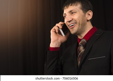 The smiling talking businessman in black suit is using phone on black background.