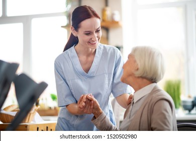 Smiling and talking. Red-haired caregiver smiling and talking to aged woman while taking care of her