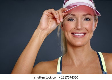 Smiling tanned fit woman in pink transparent sun cap.