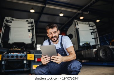 Smiling tattooed bearded blue collar worker in overalls using tablet to check on delivery while crouching in garage of import and export firm. In background are trucks.