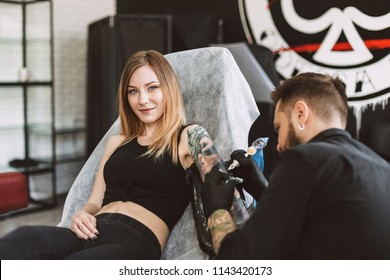 Smiling tattooed girl looking in camera while professional tattooer doing tattoo on hand using tattoo machine in studio