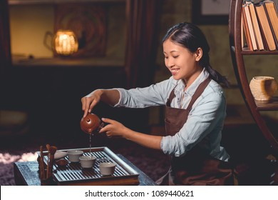 Smiling tea master pouring tea from teapot indoors