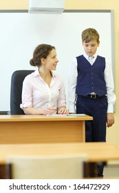 Smiling teacher checks exercise book and boy looks at her in classroom at school. Focus on woman.