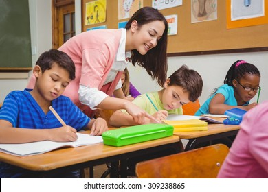 Smiling teacher helping a student at the elementary school