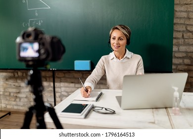 Smiling teacher holding online lecture from the classroom during COVID-19 lockdown.