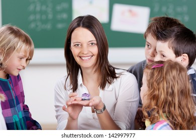 Smiling teacher holding purple stone on her hand in science class