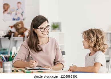 Smiling teacher listening to autistic boy in the classroom