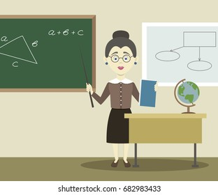 Smiling teacher standing in front of blackboard with pointer.