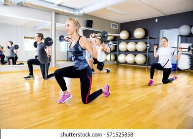 Smiling team do split squats with weights at fitness gym